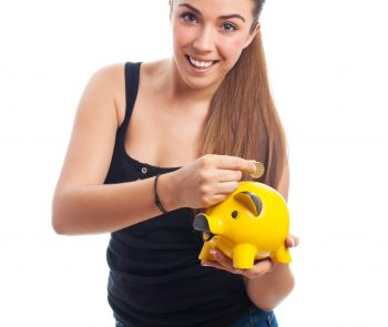 portrait of a young woman inserting coin in a piggy bank
